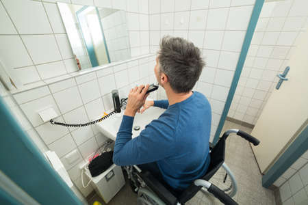 Disabled Man On Wheelchair Trimming Beard In Bathroom