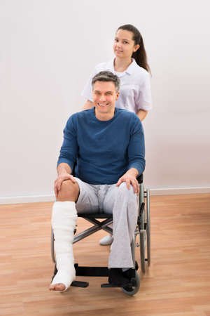plaster foot: Nurse Assisting Disabled Patient Sitting On Wheelchair Stock Photo