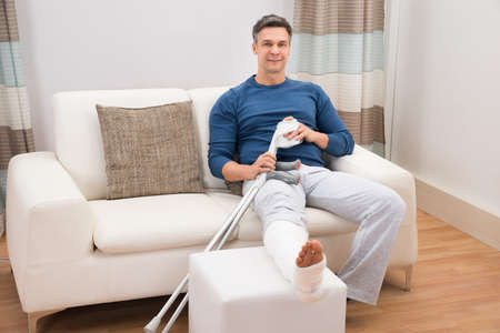 pierna rota: Retrato de un hombre sentado en el sofá Sonriente Con Muletas At Home