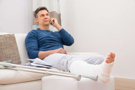 damaged: Man With Fractured Leg Sitting On Sofa Talking On Cellphone Stock Photo