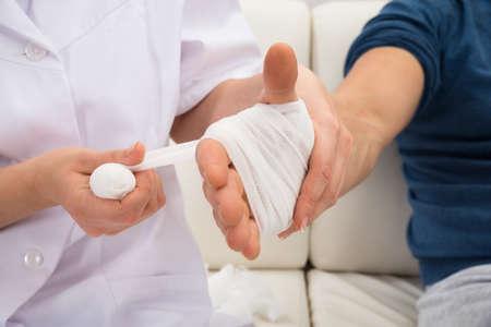 Close-up Of A Nurse Bandaging Patient's Hand Standard-Bild