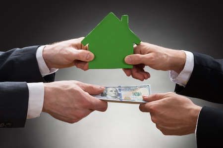 installment: Close-up Of Businesspeople Hands Holding Green House Model And Money