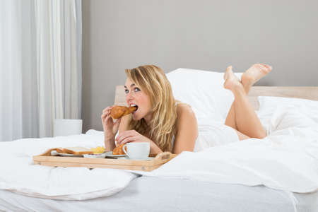 sheets: Photo Of Young Woman Having Breakfast In Bedroom