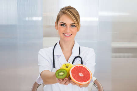 dietician: Portrait Of Happy Female Dietician Holding Fruits Stock Photo