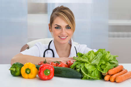dietician: Portrait Of Female Dietician With Vegetables On Desk