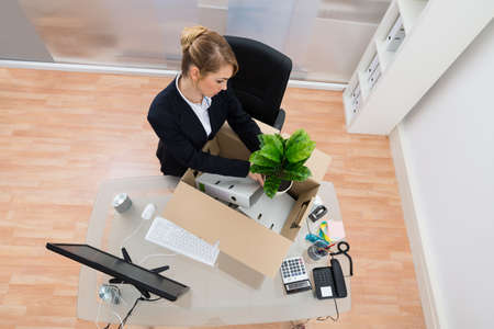 belongings: High Angle View Of Businesswoman Packing Belongings In Cardboard Box Stock Photo