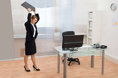 violence in the workplace: Angry Businesswoman Standing At Desk Throwing Laptop In Office Stock Photo