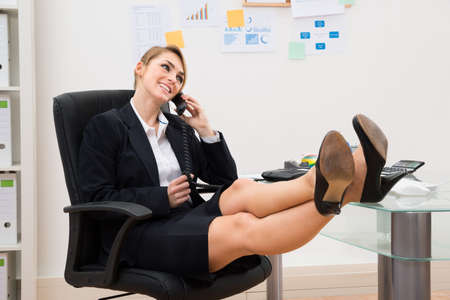 businesswoman legs: Young Happy Businesswoman With Feet On Desk While Talking On Telephone