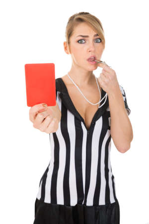 Portrait Of Female Referee Holding Red Card While Blowing Whistle photo