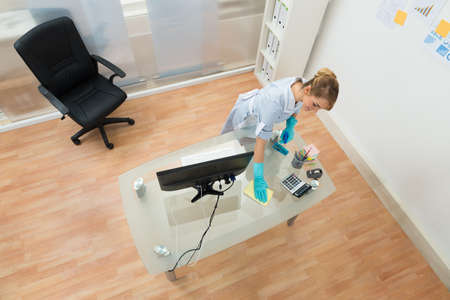 High Angle View Of Young Maid Cleaning Desk In Office Standard-Bild