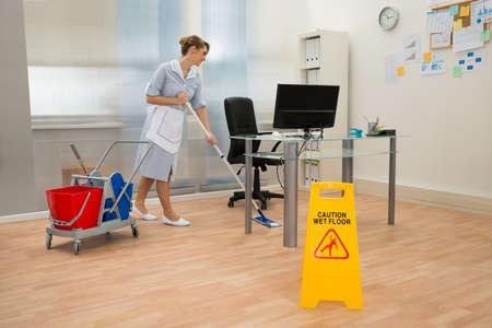 mucama: Joven Planta de limpieza de la criada con la fregona en oficina