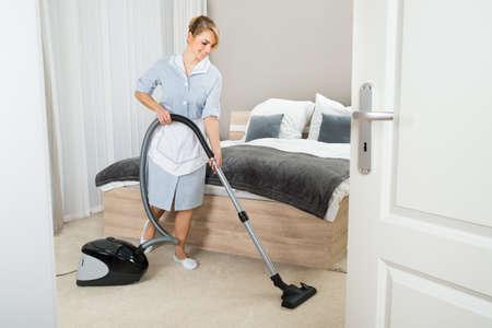 maid: Joven criada Limpieza En La Habitación Con Aspiradora