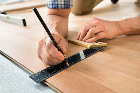 new construction renovation: Close-up Of A Worker Drawing A Mark On Laminate Using Ruler