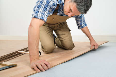 hardwood flooring: Carpenter Installing New Laminated Wooden Floor At Home Stock Photo