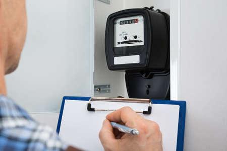 contador electrico: Técnico Escritura Lectura De Meter en el sujetapapeles Foto de archivo