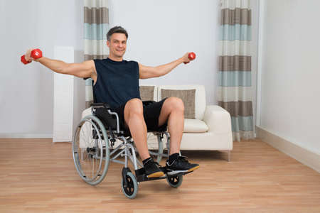 injured person: Handicapped Man On Wheelchair Working Out With Dumbbell At Home