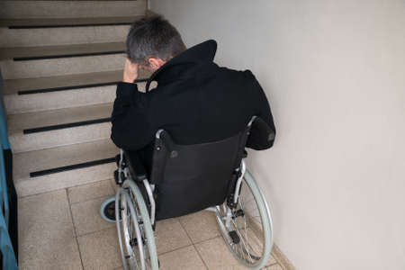 Rear View Of A Worried Disabled Man In Front Of Staircase