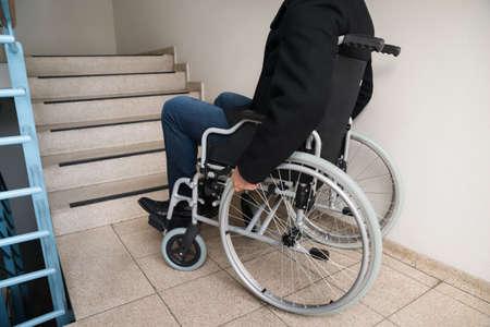 silla de rueda: Primer plano del hombre desactivado en silla de ruedas delante de la escalera