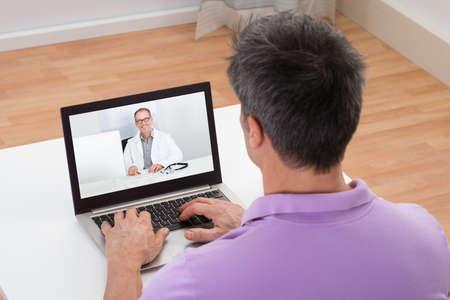 consulta médica: Hombre que tiene Video Chat con el médico en la computadora portátil en casa