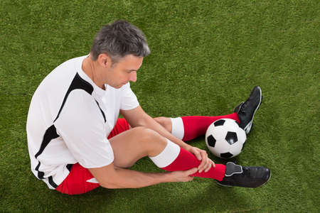 Male Soccer Player With Injury In Leg On Field photo