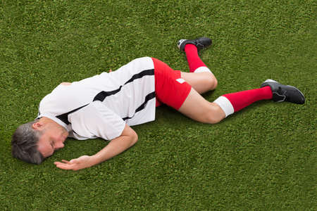 uniform green shoe: Male Soccer Player Suffering From Injury Lying On Grass