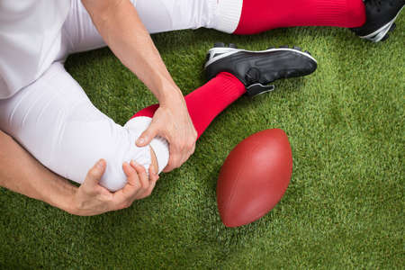 leg injury: Close-up Of A American Football Player With Injury In Leg On Field