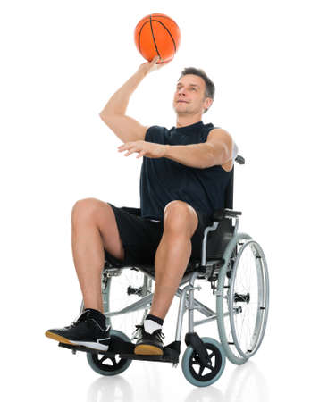 recovering: Handicapped Basketball Player On Wheelchair Throwing Ball Over White Background