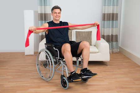 resistance: Handicapped Man On Wheelchair Exercising With Resistance Band At Home Stock Photo