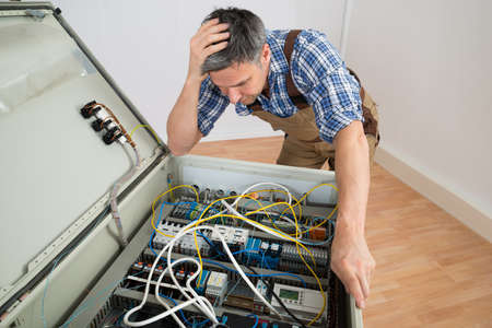 fuse: Portrait Of A Confused Electrician Looking At Fuse Box Stock Photo