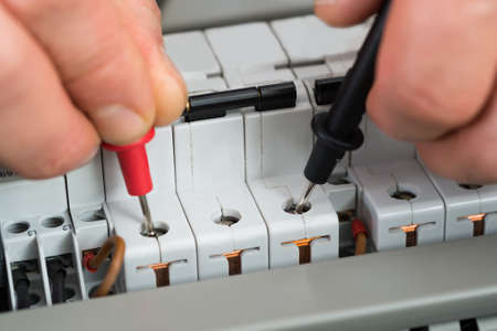 manual test equipment: Close-up Of A Technician Checking Fuse With Multimeter Stock Photo