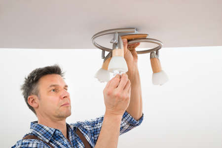 wirework: Portrait Of A Male Electrician Fixing Light On Ceiling