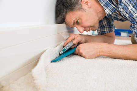 carpet: Close-up Of A Craftsman Cutting Carpet With Cutter Stock Photo