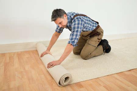 Männliche Arbeitnehmer Unrolling Teppich Stock zu Hause Standard-Bild - 40366173