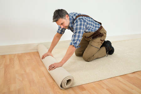 hardwood: Male Worker Unrolling Carpet On Floor At Home