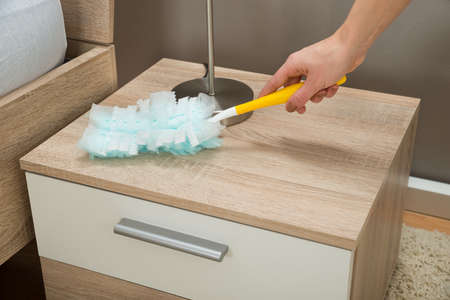 removing: Close-up Of Hand Removing Dust From Nightstand With Duster Feather