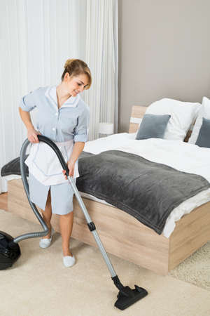vacuum cleaner: Happy Female Housekeeper Cleaning Floor With Vacuum Cleaner In Hotel Room