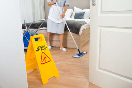hotel room door: Female Maid Cleaning Floor In Hotel Room
