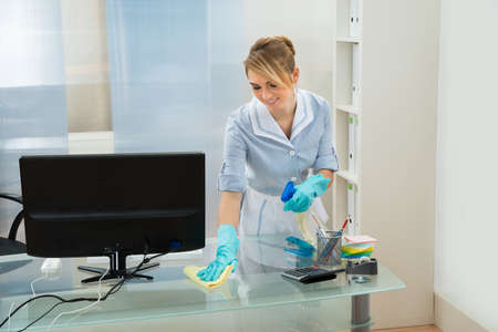 office: Young Female Maid Cleaning Glass Desk With Feather Duster In Office