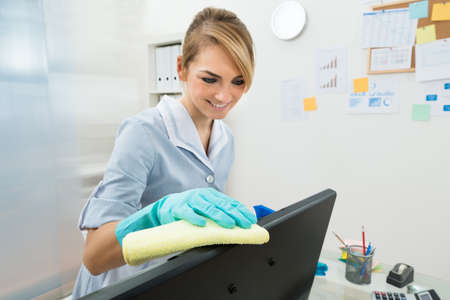 Portrait Of Young Happy Maid Cleaning Computer In Office photo