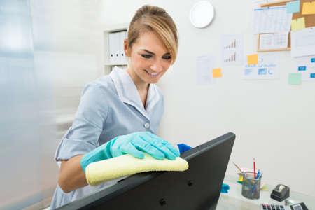 sirvienta: Retrato de joven feliz de la criada de limpieza en equipo en la oficina Foto de archivo