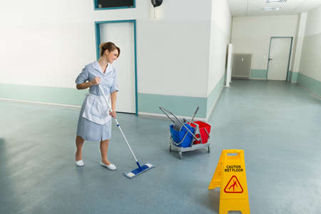 janitor: Young Happy Female Janitor Cleaning Floor With Mop