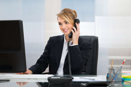 workplace wellness: Young Happy Businesswoman Talking On Telephone At Desk In Office Stock Photo