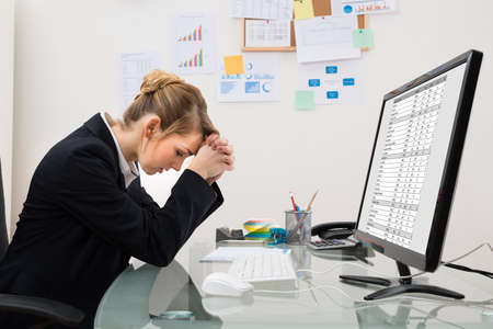 spreadsheets: Stressed Young Businesswoman Sitting At Desk In Office