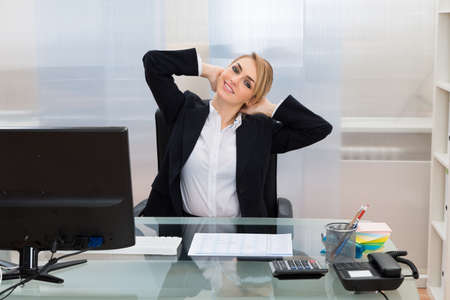 workplace wellness: Young Happy Businesswoman With Hands Behind Head Sitting At Desk Stock Photo