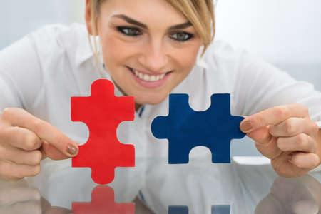 jigsaw puzzle pieces: Portrait Of Happy Businesswoman Holding Pieces Of Jigsaw Puzzle On Desk