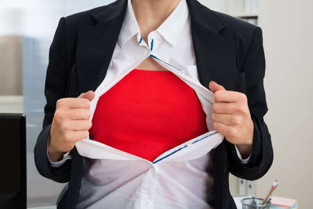 Close-up Of Businesswoman In Office Tearing Off Her Shirt Showing Red Costume Stock Photo