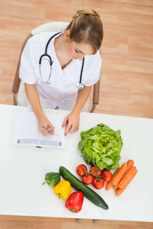dietician: High Angle View Of Female Dietician Writing Prescription With Vegetables On Desk