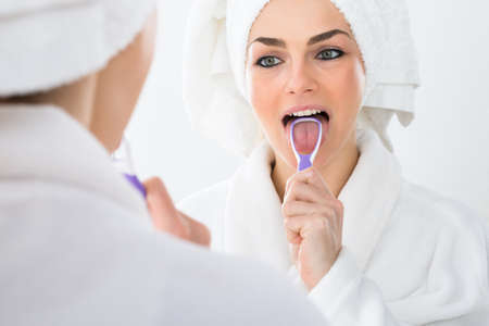 bad hygiene: Close-up Of A Woman Looking In Mirror Cleaning Her Tongue