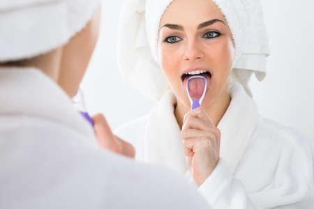 Close-up von einer Frau im Spiegel schaut Reinigung ihre Zunge