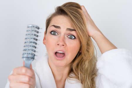 cabello rubio: Preocupado mujer que sufre de Hairloss Mirando a Peine Foto de archivo